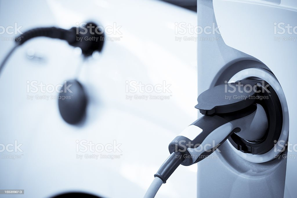 Electric vehicle charging, focus on foreground stock photo
