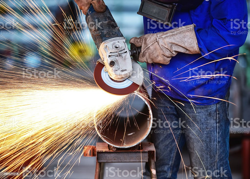 Electric wheel grinding on steel pipe in factory stock photo