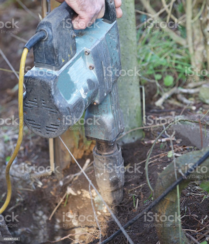 Electrical breaker breaking out concrete around an old fencing post stock photo