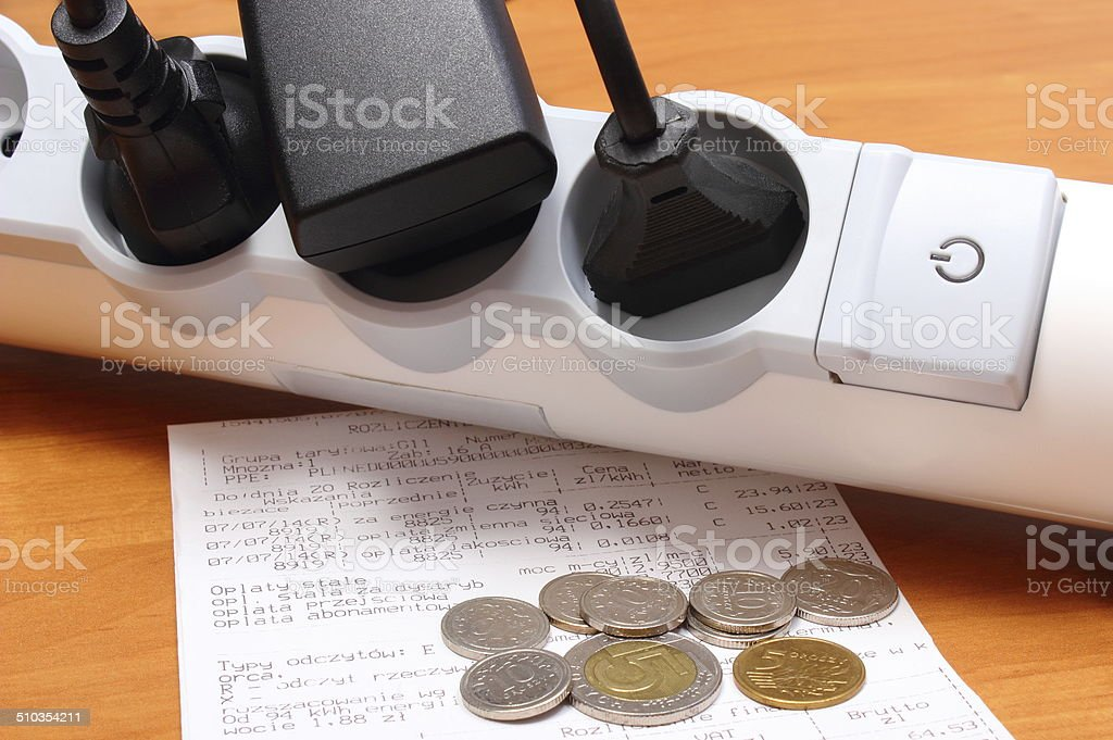 Electrical cords connected to power strip and electricity bill stock photo
