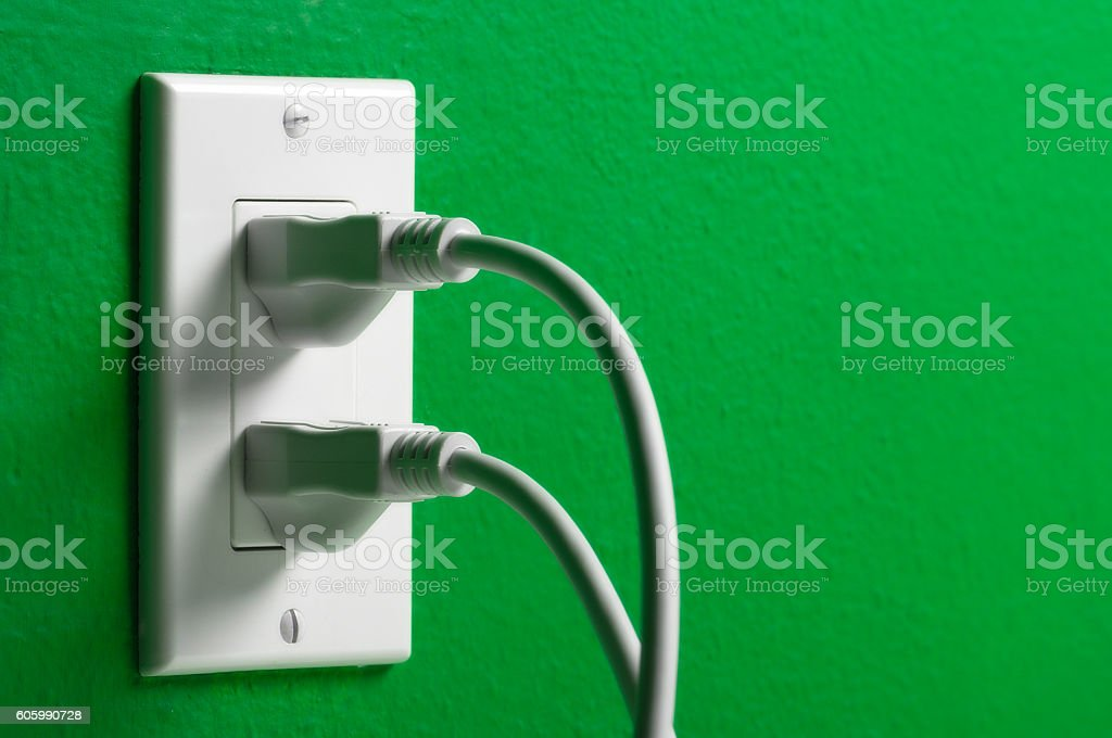 Electrical cords plugged white outlet on a green wall stock photo