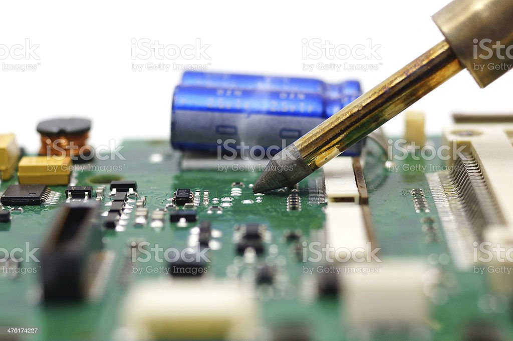 Electrical Engineer is soldering on printed circuit board stock photo