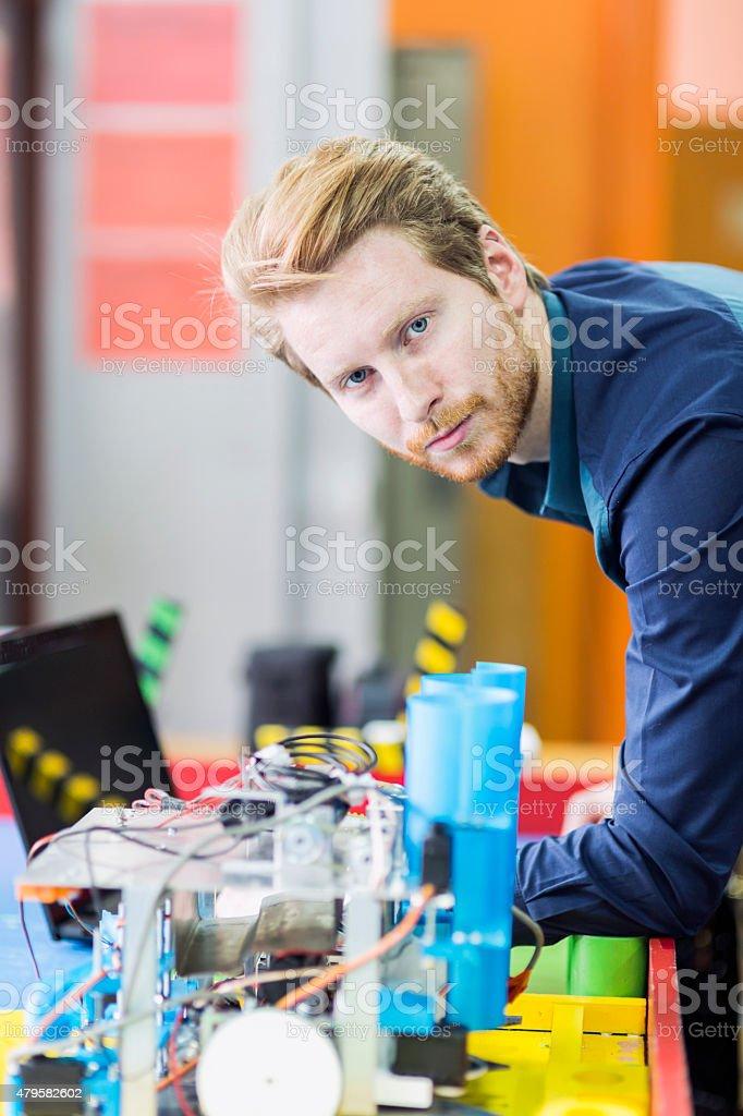 Electrical engineer programming a robot during robotics class stock photo