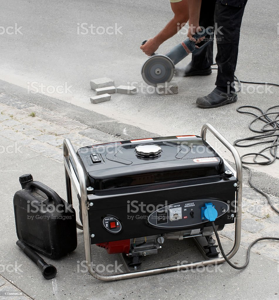 Electrical generator in foreground and man using masonry saw stock photo