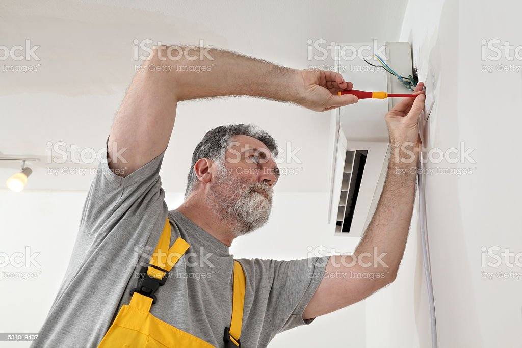 Electrical installation of air conditioner, electrician at work stock photo