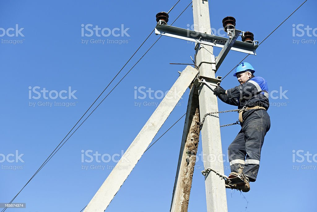 Electrical lineman working at the top of the pole stock photo