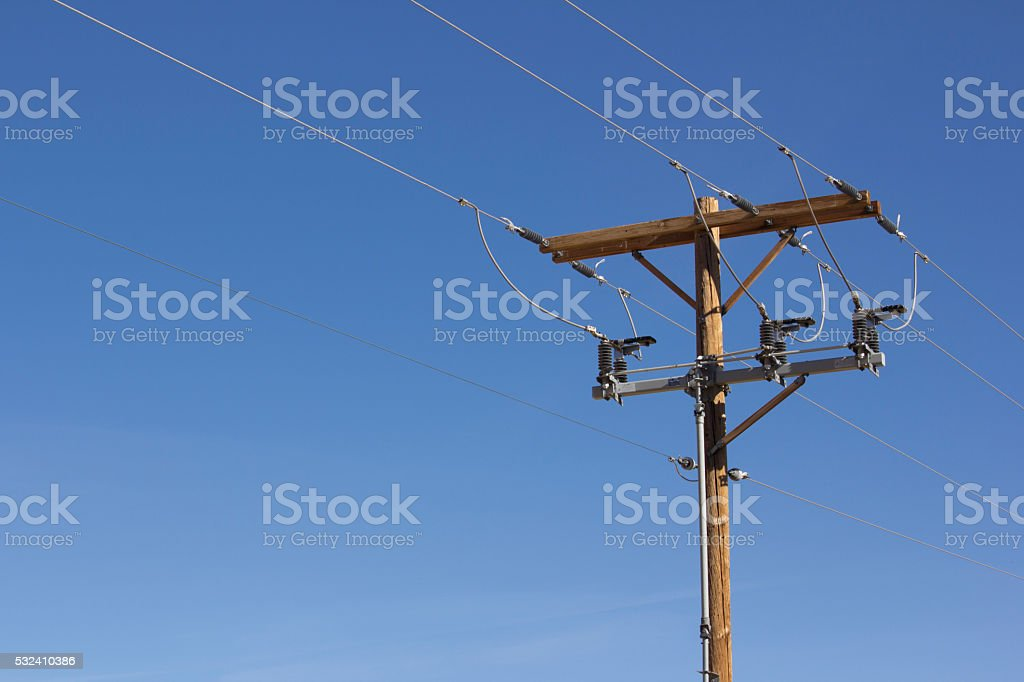 Electrical pole with a bright blue background stock photo