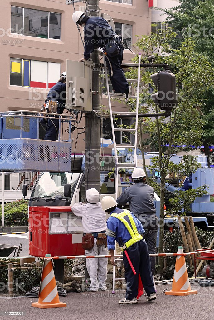 Electrical team working on a city pole royalty-free stock photo
