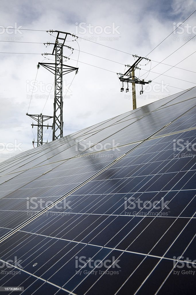 Electrical towers behind energy grid panels with sky royalty-free stock photo