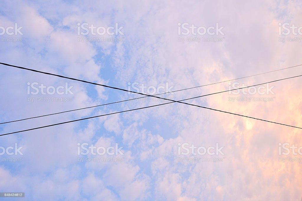 Electrical wires crossing over each other in the evening sky foto de stock libre de derechos