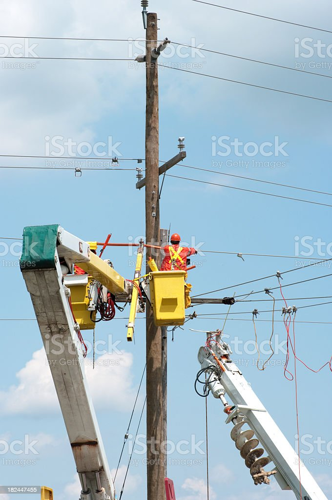 Electrical Worker by High Voltage Power Line stock photo