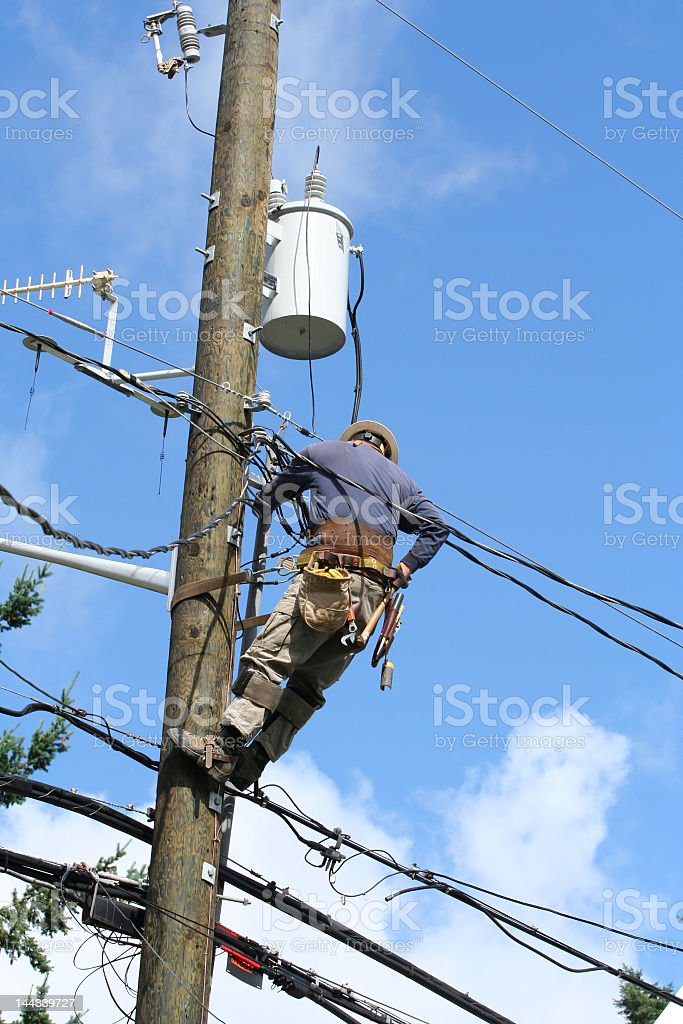 Electrical worker working on electrical wire line royalty-free stock photo
