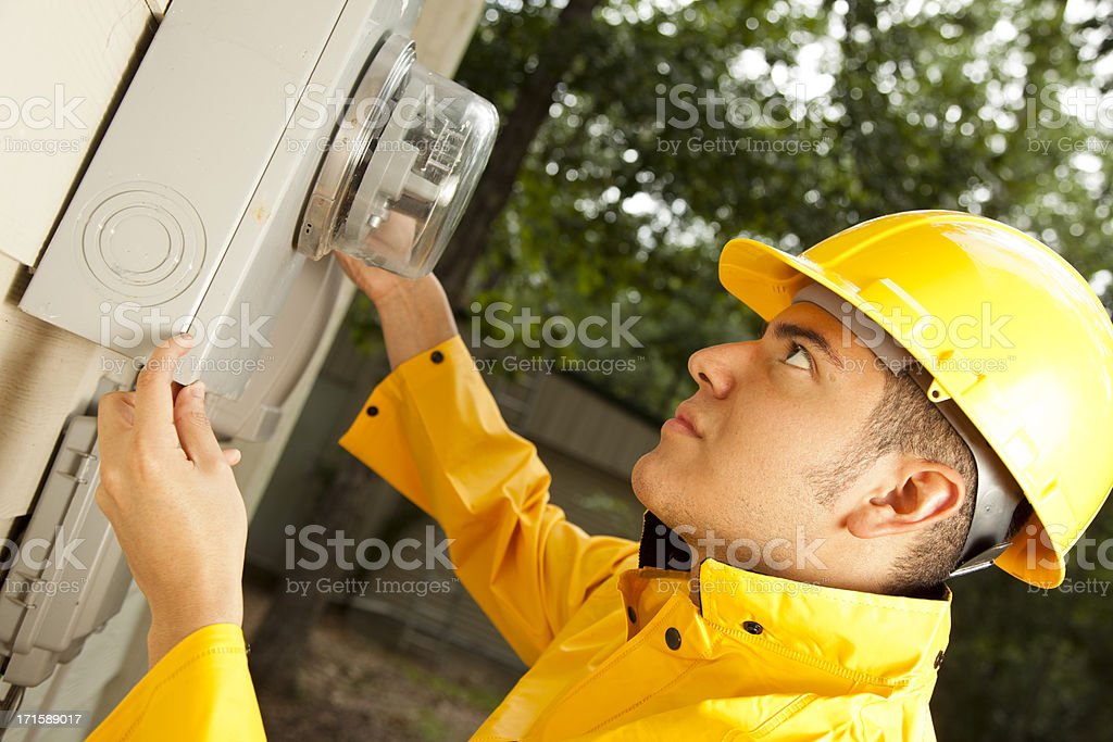 Electrician at outside electric meter on home stock photo