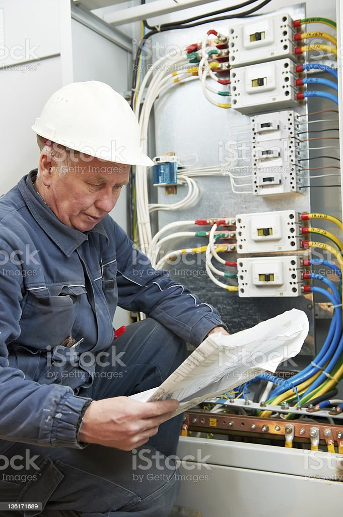 Electrician at wiring with working drawings royalty-free stock photo