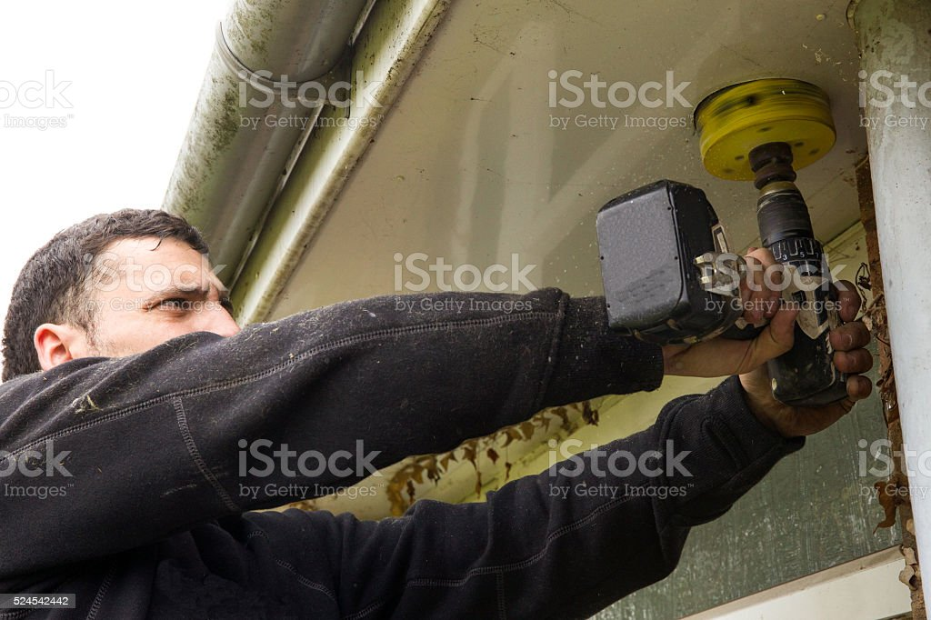 Electrician builder manual worker drilling a rotary hole stock photo