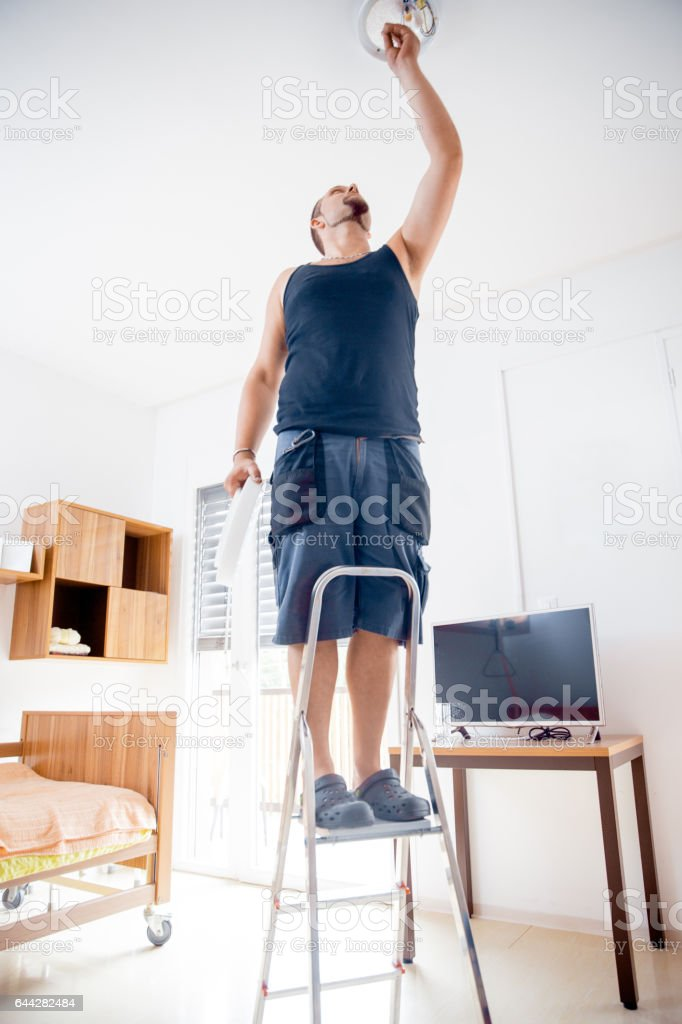 Electrician Changing Light Bulb In The Elderly Center stock photo
