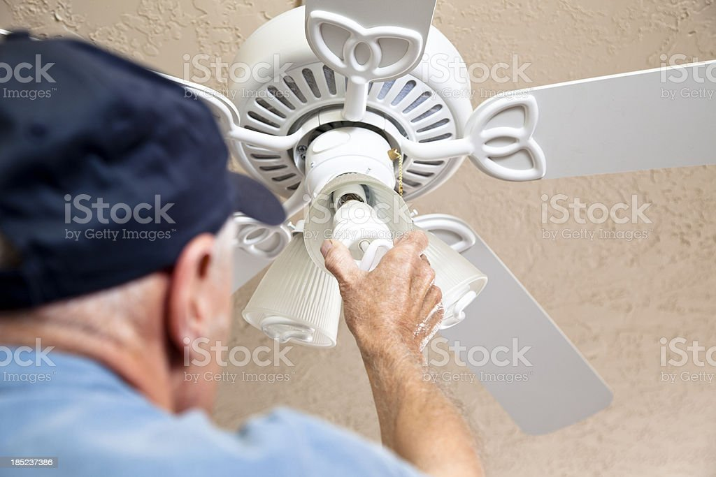 Electrician changing out light bulbs to eco-friendly compact fluorescent stock photo