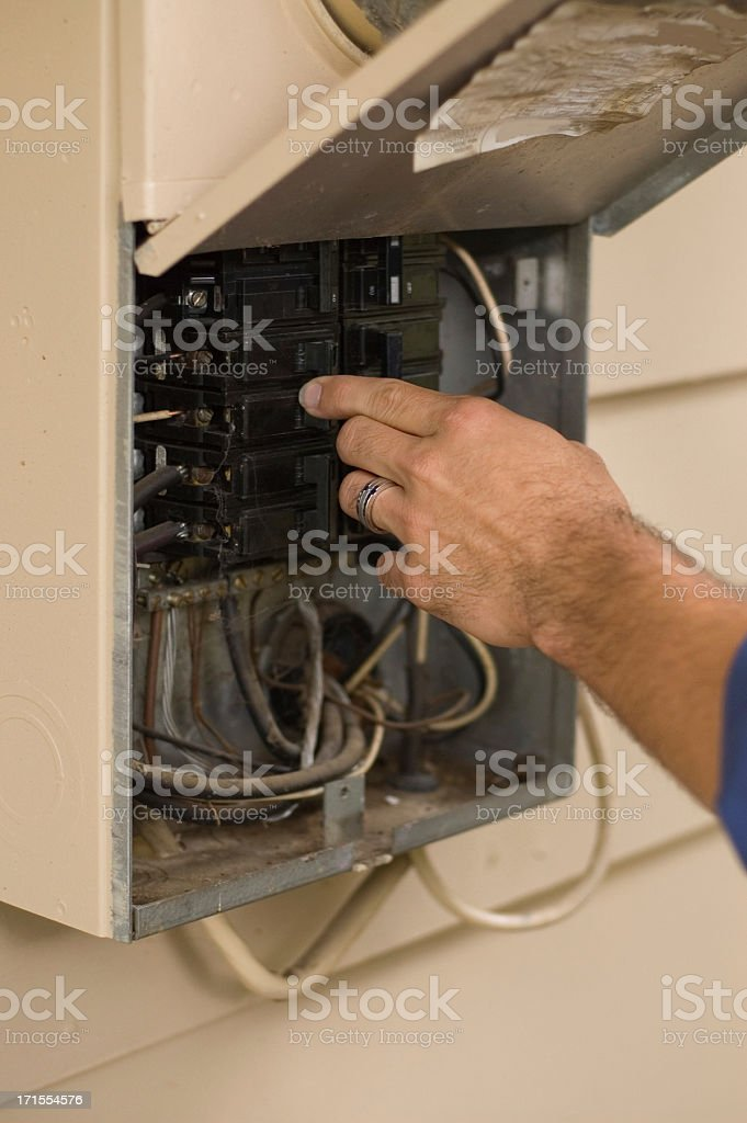 Electrician checking a breaker box. royalty-free stock photo