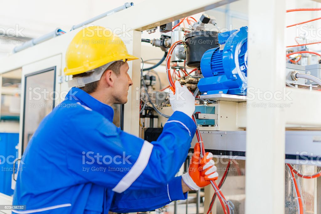 Electrician checking wires and cables on machine in factory stock photo