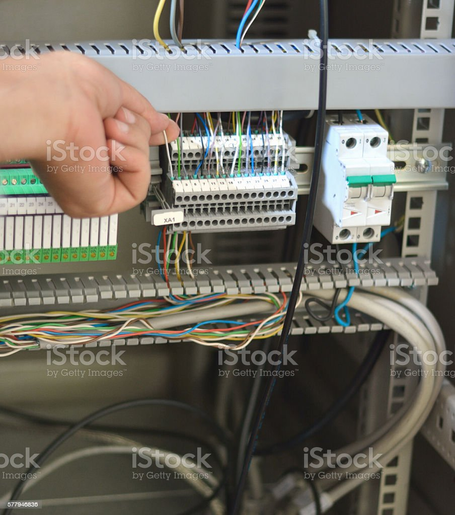 Electrician Checking Wires, Terminal Blocks, Electrical Fuses and PLC Relay stock photo