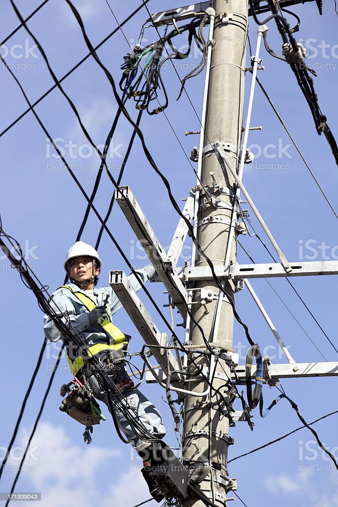 Electrician climbing up on telephone pole with pylon stock photo
