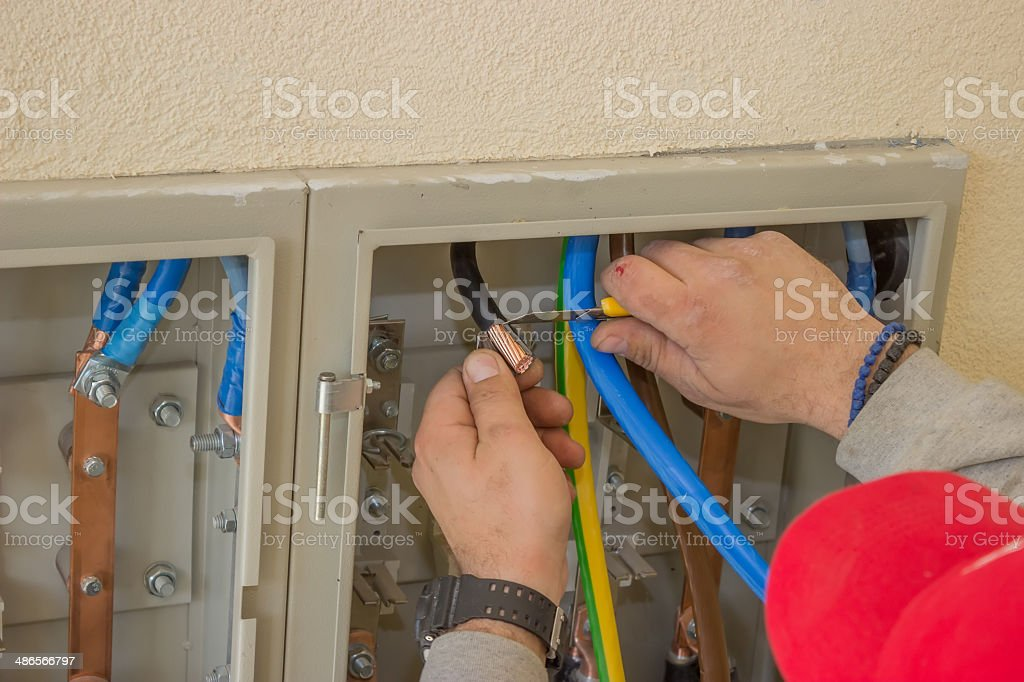 Electrician connecting wires in the electrical cabinet stock photo