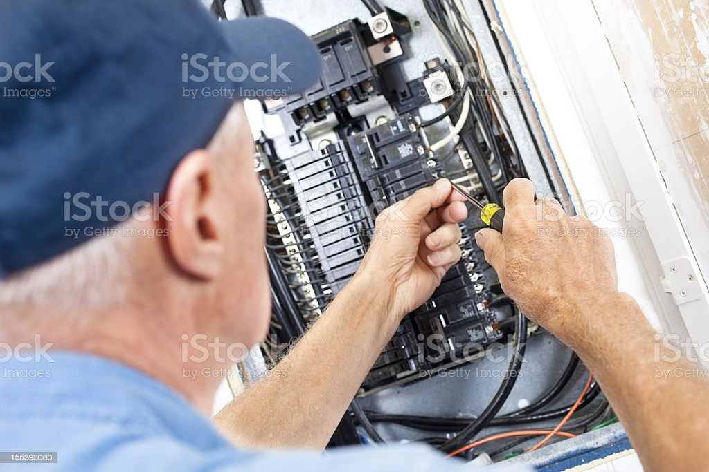 Electrician doing electrical work in breaker box stock photo