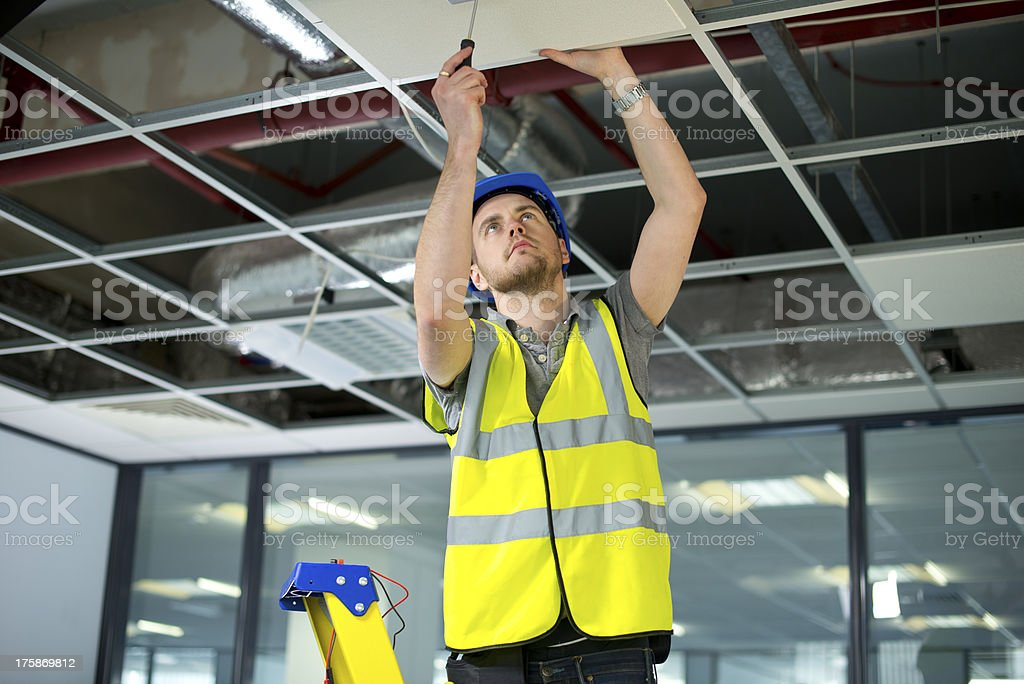 electrician fitting fire alarm to office interior stock photo