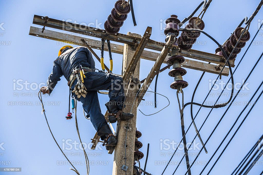 Electrician hanging on the electricity pole stock photo