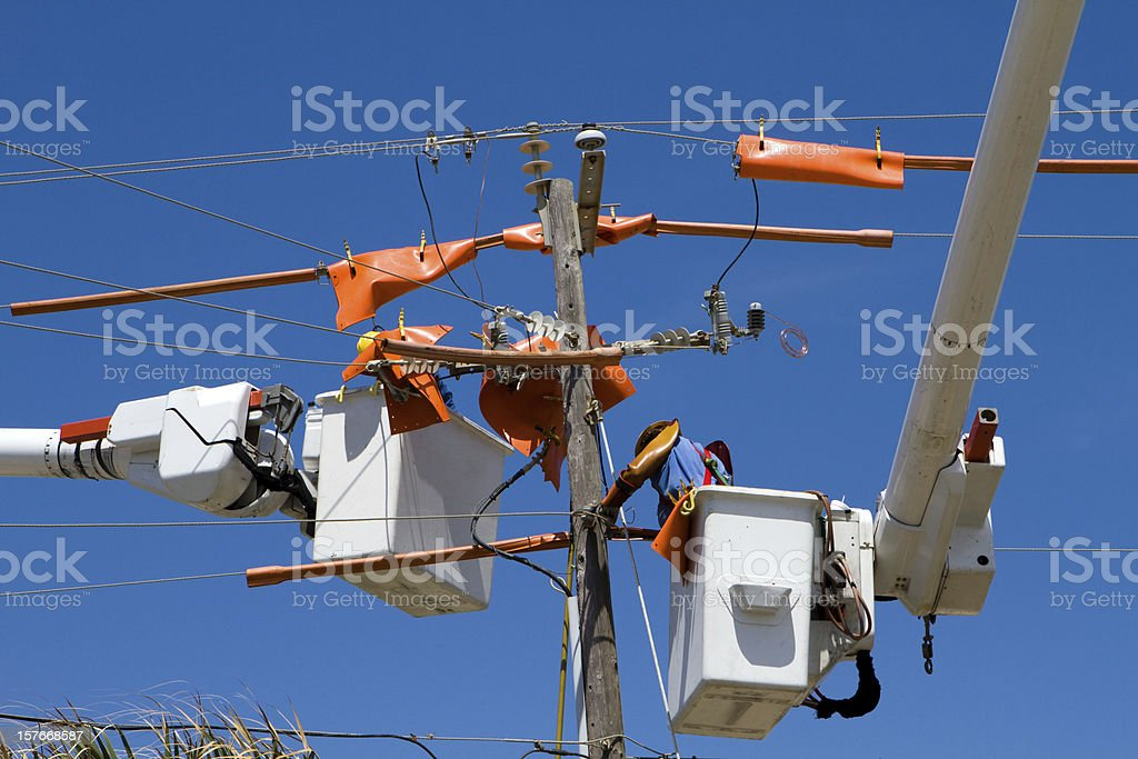 Electrician in cherry picker working on powervlines stock photo