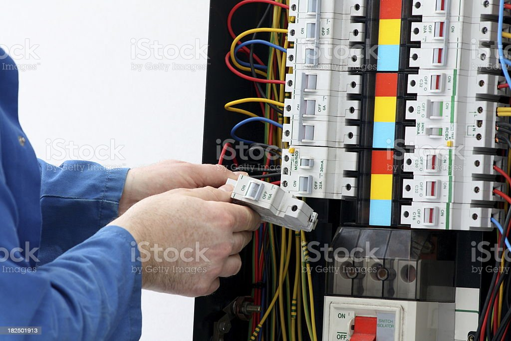 Electrician installing  circuit breaker in a fuse box. stock photo