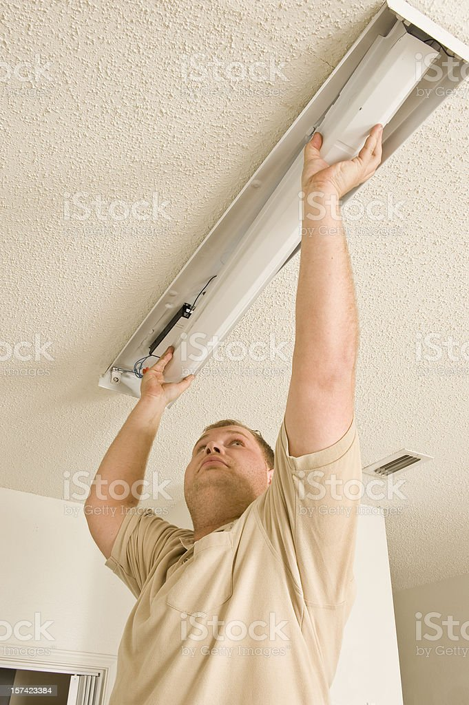 Electrician Installing Fluorescent Lighting stock photo