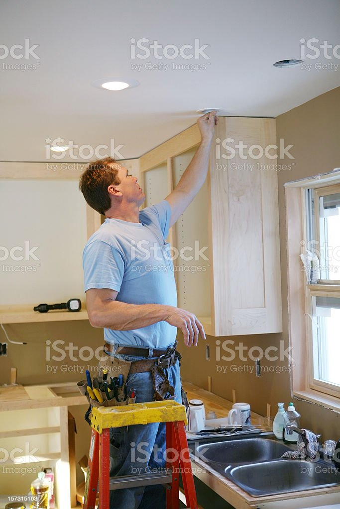 Electrician Installing Kitchen Light stock photo