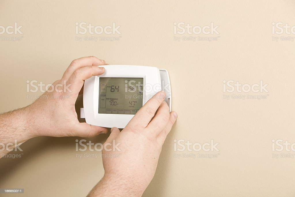 Electrician Installing New Programmable Thermostat royalty-free stock photo