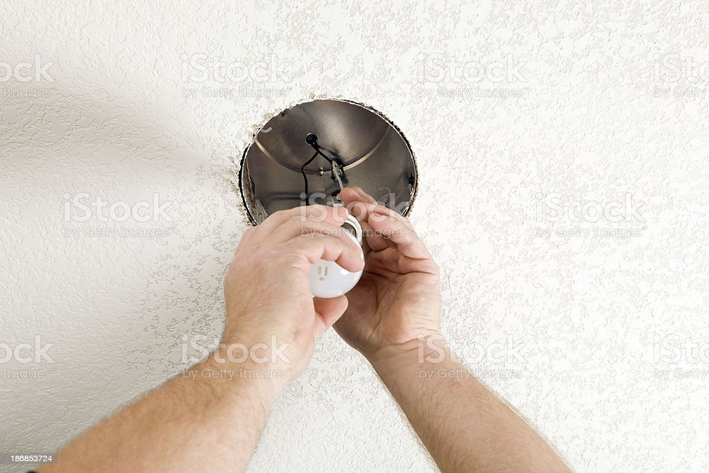 Electrician Installs 100W Light Bulb into a New Recessed Fixture stock photo