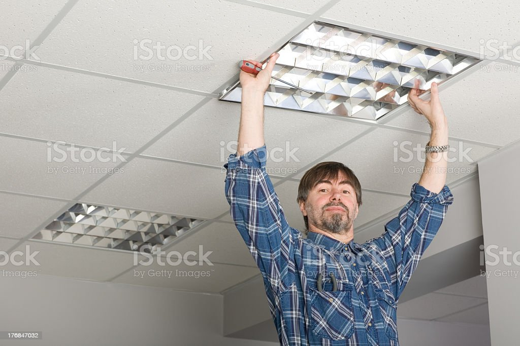 Electrician installs lighting to the ceiling. stock photo