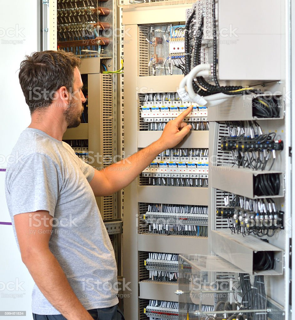 Electrician Looking in Fuse Box in Electrical Room stock photo
