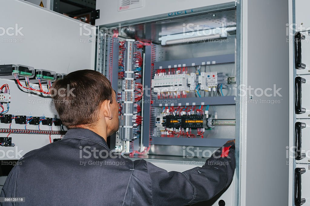 Electrician near the low-voltage cabinet. Uninterrupted power supply. Electricity. stock photo