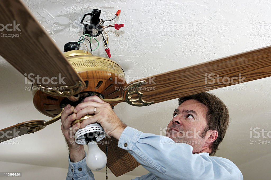 Electrician Removes Ceiling Fan stock photo
