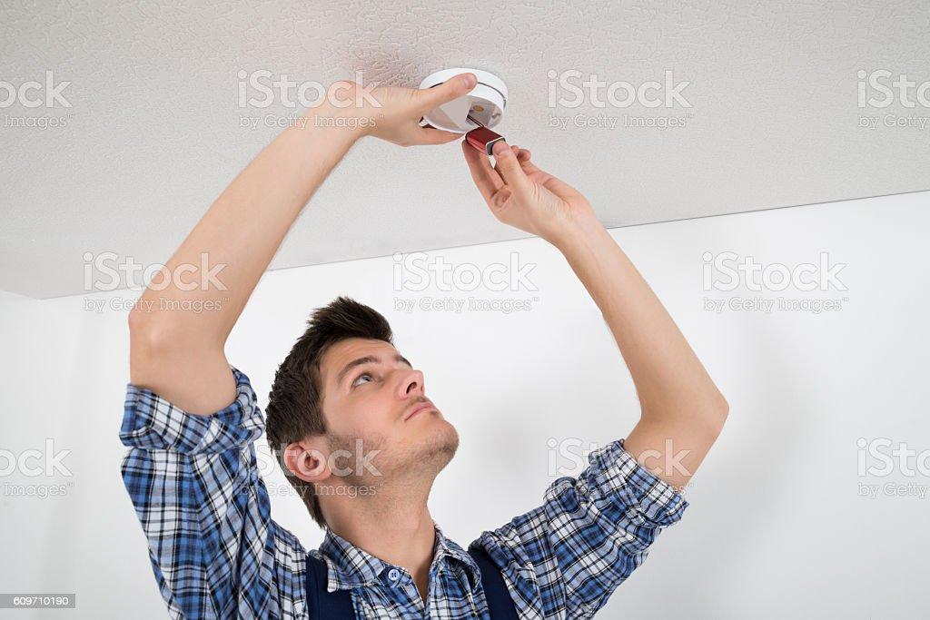 Electrician Repairing Smoke Detector stock photo