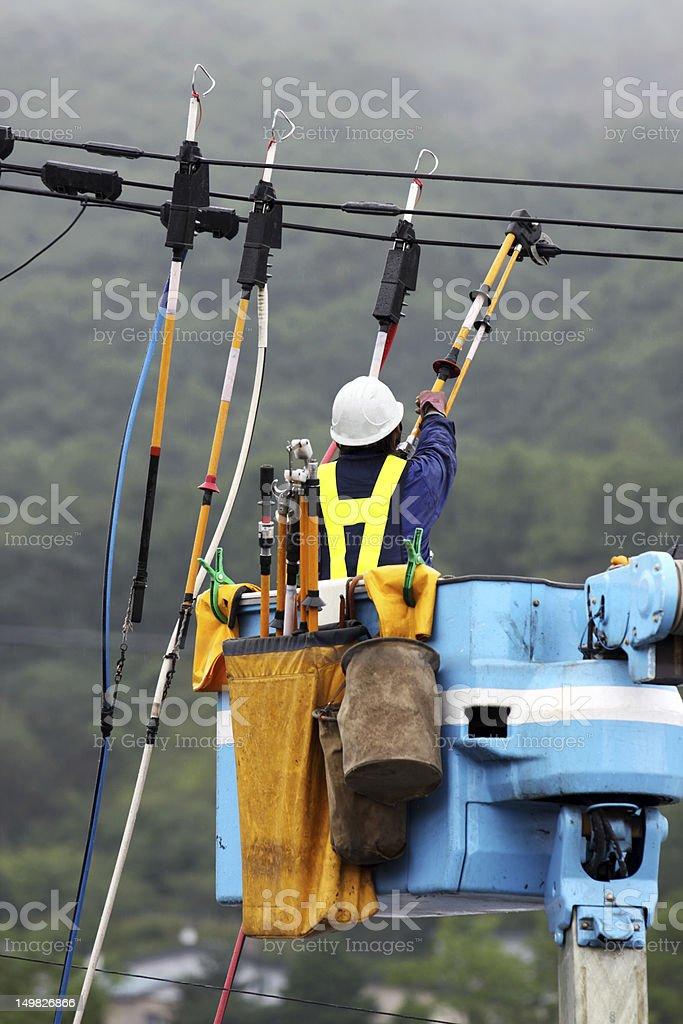 Elektriker Reparaturen eine power line unter den fallenden Regen Lizenzfreies stock-foto