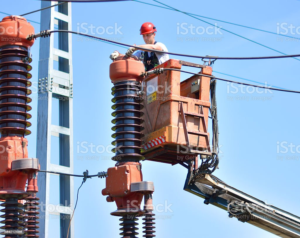 Electrician repairs insulator in power substation stock photo