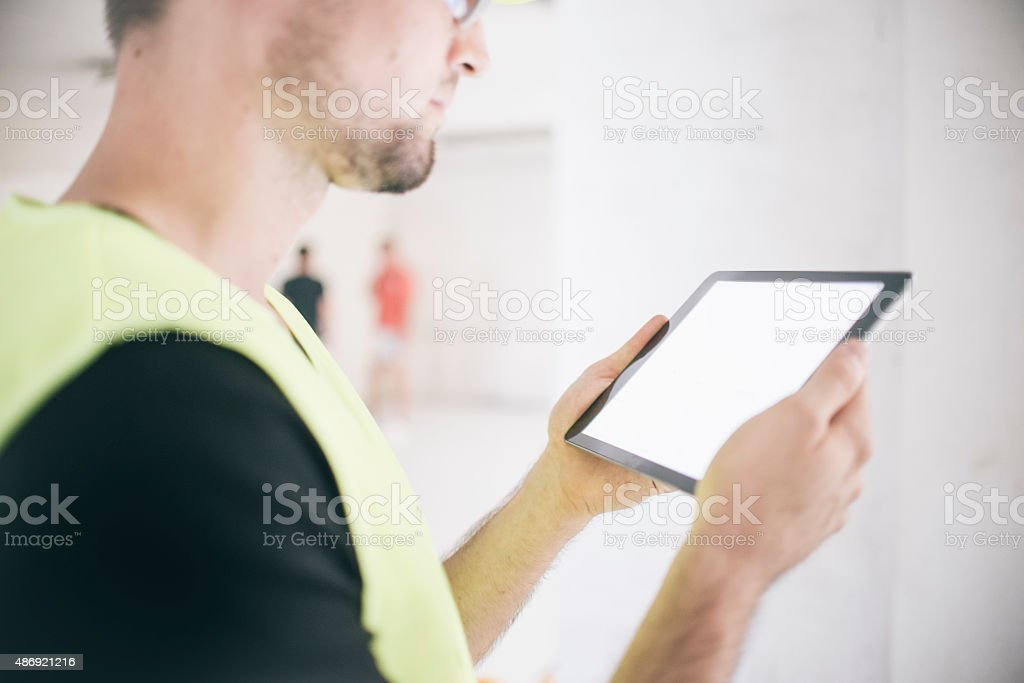 Electrician reviewing plans on digital tablet at construction site stock photo