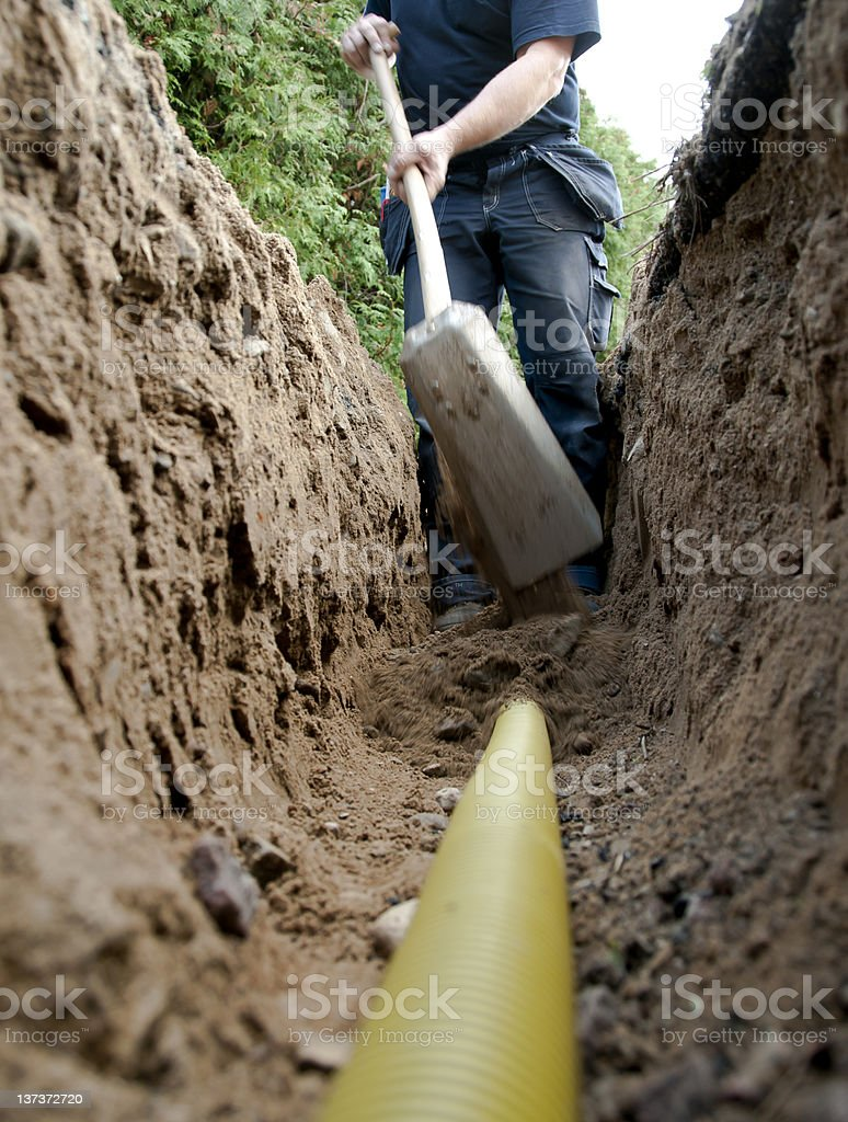 Electrician shoveling dirt in trench stock photo
