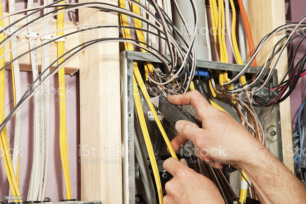 Electrician Stripping Breaker Panel Wire with Utility Knife stock photo