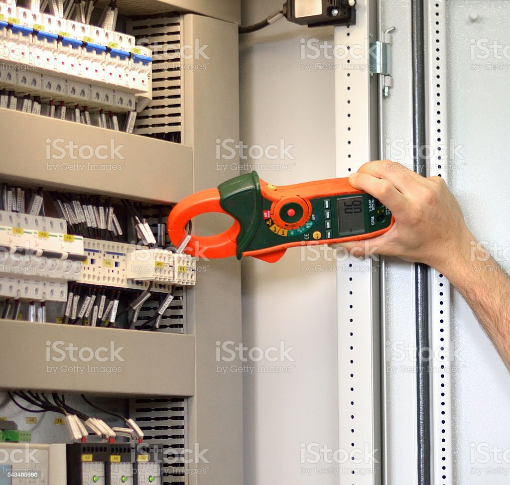Electrician Testing for Amperage on Contactor with Clamp Meter stock photo