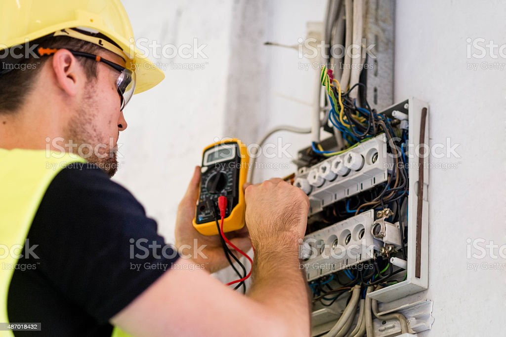 Electrician testing for voltage in a fuse box stock photo