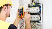 Electrician testing for voltage in a fuse box