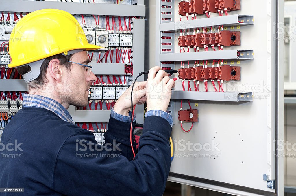 electrician testing industrial control panel stock photo
