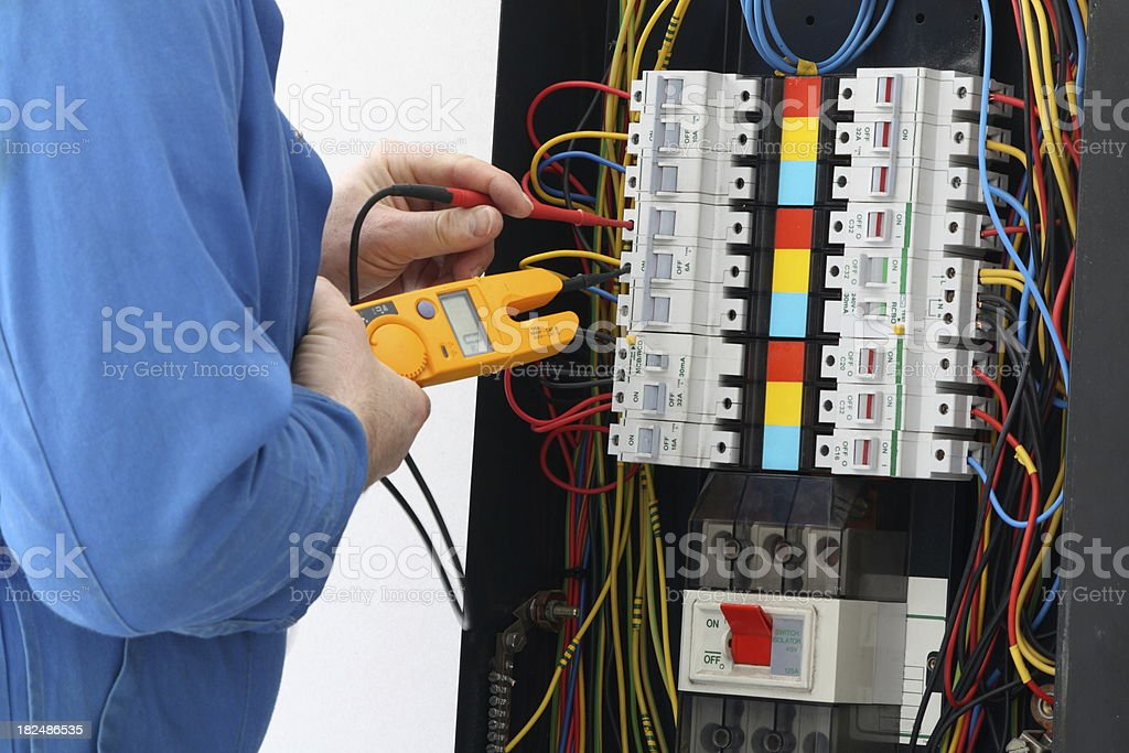 Electrician testing voltage at a fuse box. stock photo